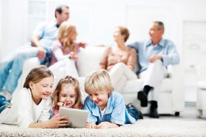 Cheerful kids lying on the carpet at their house and using a touchpad with their parents and grandparents in the background.  [url=http://www.istockphoto.com/search/lightbox/9786682][img]http://dl.dropbox.com/u/40117171/children5.jpg[/img][/url] [url=http://www.istockphoto.com/search/lightbox/9786778][img]http://dl.dropbox.com/u/40117171/family.jpg[/img][/url]